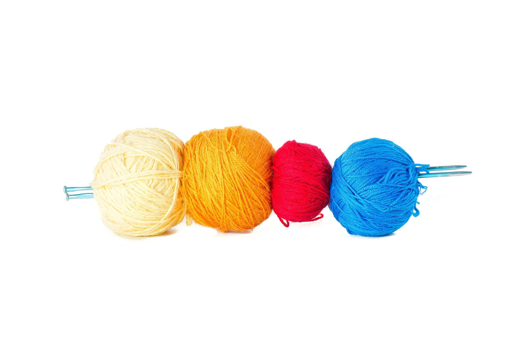 Four balls of colored wool skewered by knitting needles.